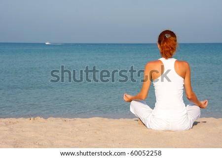 Woman meditating on the beach - stock photo