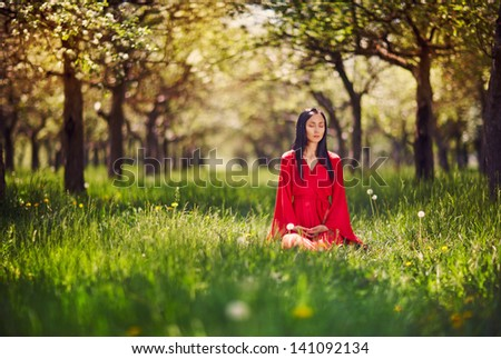 woman meditating on the grass - stock photo
