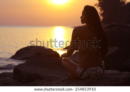 woman meditating on the sea sun beach - stock photo
