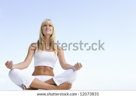 Woman meditating outside against blue sky - stock photo