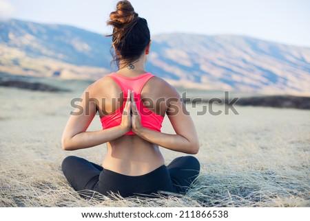 Woman meditating practicing yoga outdoors - stock photo