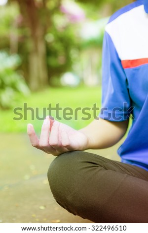 Woman meditation In the natural park with morning sun - stock photo