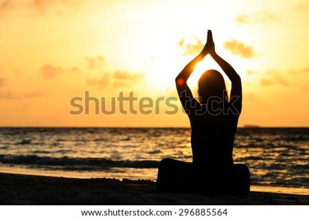 Woman meditation on sunset beach - stock photo