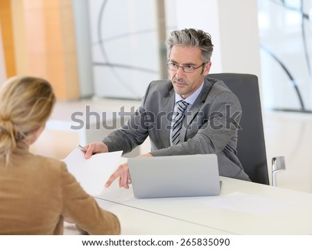 Woman meeting with banker and signing contract - stock photo