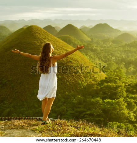 Woman meets sunrise at Chocolate hills in Bohol, Philippines - stock photo