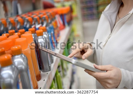 Woman merchandiser checking products available with digital tablet - stock photo