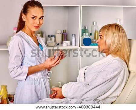 Woman middle-aged in spa salon with young beautician looking at camera. - stock photo
