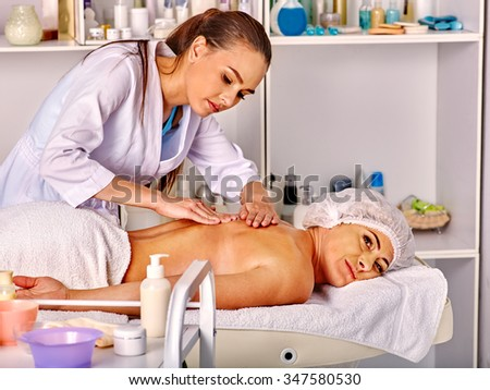 Woman middle-aged take back massage in spa salon with young beautician. Table with cosmetics in foreground. - stock photo