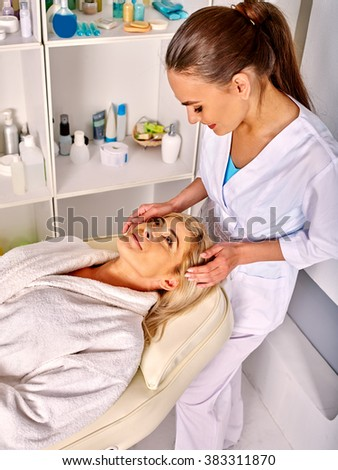 Woman middle-aged take face and neck massage in spa salon. Two people.
