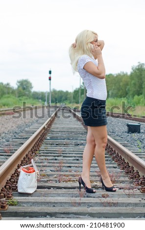 Woman missed the train. Calling someone on the phone. - stock photo