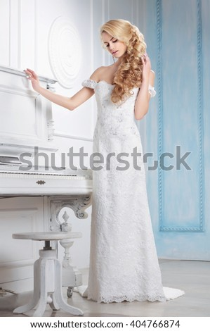 Woman model in a wedding dress posing in the interior. - stock photo
