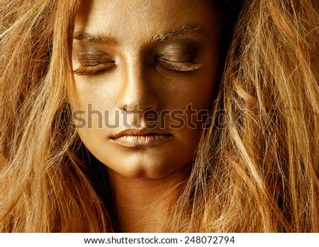 woman model with luxury makeup. Professional makeup. Golden face. - stock photo