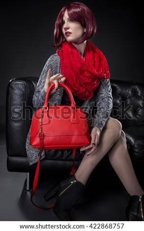 Woman modeling spring fashion and a red hand bag on a black leather couch.  She is wearing fall or spring style fashion.