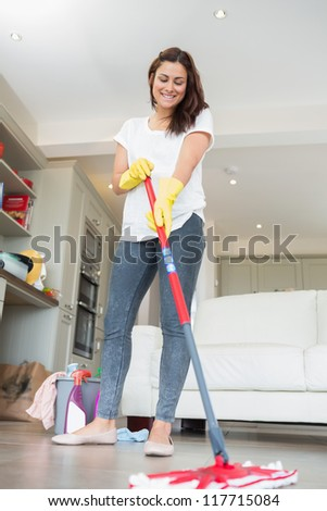 Woman mopping the floor of living room - stock photo