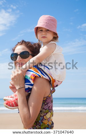 woman mother black sunglasses carrying on shoulders two years old blonde baby with pink hat white shirt and colorful trousers at summer beach  - stock photo