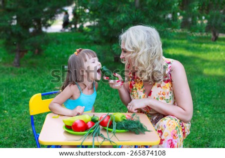 Woman mother mum feeding her girl daughter kid child with cucumber outdoors in garden
