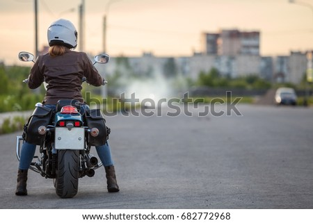 Woman motorcyclist sitting on the cruiser motorbike on urban asphalt road, rear view, copyspace