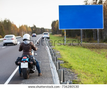 Woman motorcyclist standing on the asphalt road in front of the blank information board with blue background, autumn season