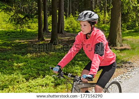 Woman mountain biking in forest on sunny day cycling path - stock photo