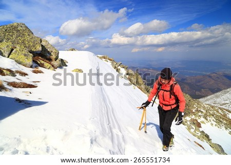 Woman mountaineer ascending snow covered summit in sunny day - stock photo