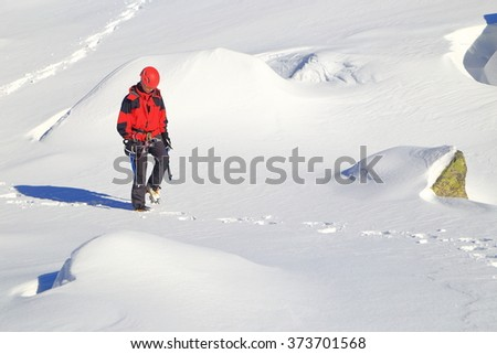 Woman mountaineer carrying ice axes on snowy trail in Retezat mountains, Romania - stock photo