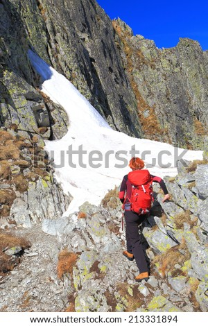 Woman mountaineer climbs on a rocky mountain in sunny day