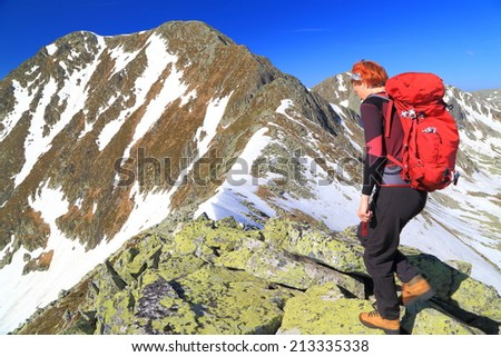 Woman mountaineer climbs on a rocky mountain in sunny day - stock photo