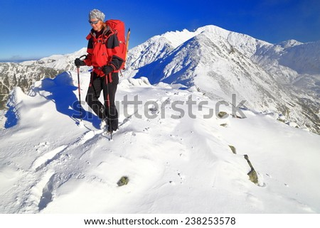Woman mountaineer follows a trail on snow covered mountain - stock photo