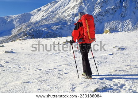 Woman mountaineer traversing a snow covered field on the mountain - stock photo