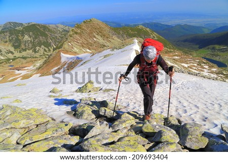 Woman mountaineer traversing a snow field on the sunny mountain - stock photo