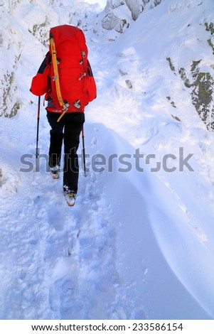 Woman mountaineer walking on snow covered mountain trail  - stock photo