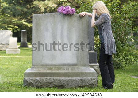 Woman mourns in cemetery resting on gravestone - stock photo