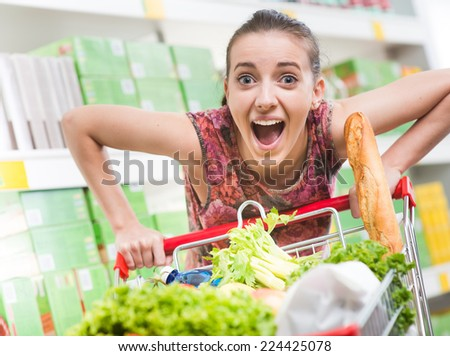 Woman mouth open pushing a full heavy shopping cart at supermarket. - stock photo