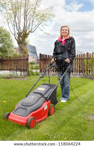 Woman mowing a garden with an electric lawn mower - stock photo