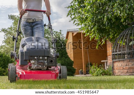 Woman mows her lawn with a red gasoline lawnmower in summer