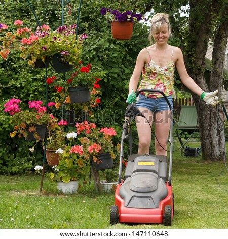 Woman mows the lawn with an electric lawn mower - stock photo
