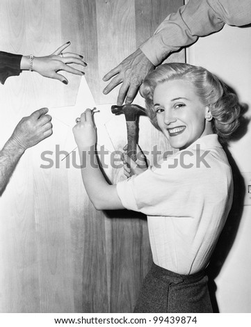 Woman nailing up star with helping hands - stock photo