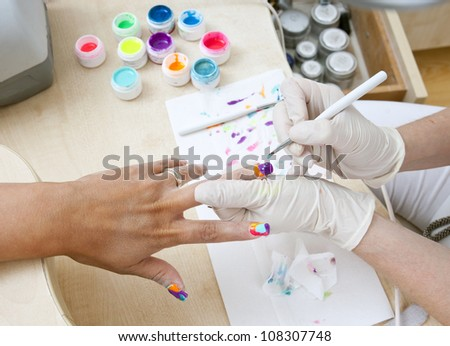 woman nails get painted in manicure salon - stock photo