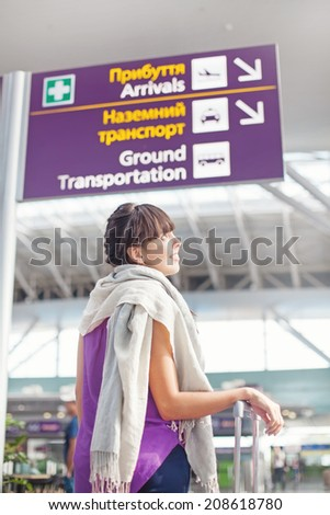 Woman navigating in airport alone - stock photo