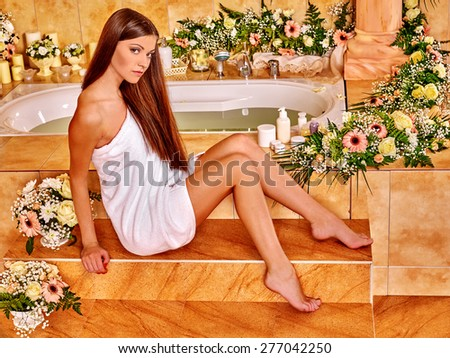 Woman near bath relaxing at water spa. - stock photo