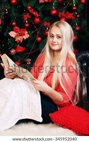 Woman near Christmas tree reads a book
