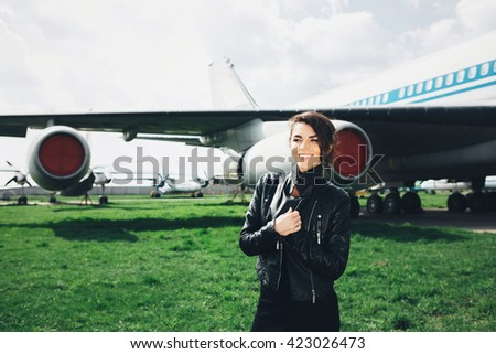 Woman near the aircraft.Travel.Enjoy moment.Wait somebody.Woman is waiting for a flight