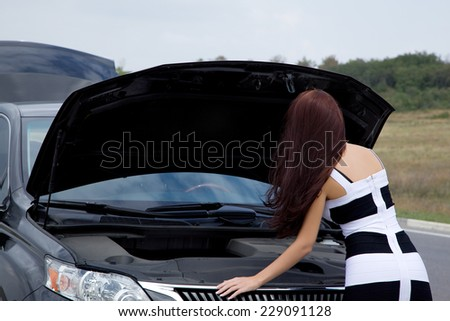 Woman near the car with the hood open in a difficult situation - stock photo
