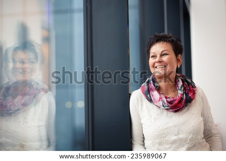 Woman near window area looking and smiling.