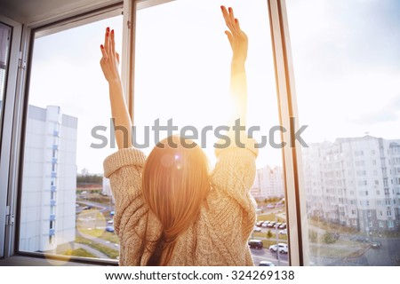 Woman near window raising hands facing the sunrise at morning - stock photo