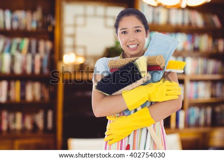 Woman nearly dropping her cleaning tools against view of studio - stock photo