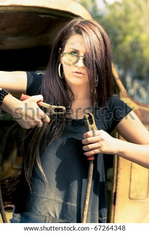 Woman Needing A Power Boost Stands Beside Her Broken Down Old Vehicle On The Road Side Holding Car Jumper Leads Hoping For A Positive Electrical Energy Surge - stock photo