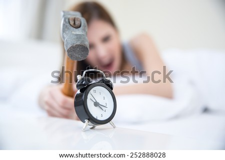 Woman not wanting to get up, taking a hammer to her alarm clock. Focus on clock - stock photo