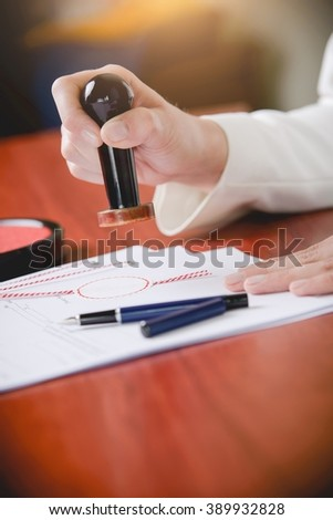 Woman Notary Public stamping the document. Law office. - stock photo