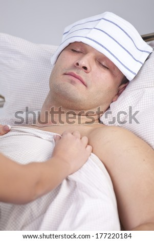 Woman nursing a sick man on the bed - stock photo